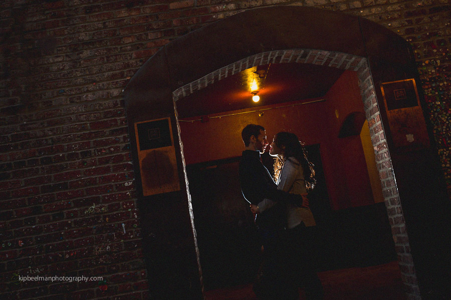 A couple move from their University of Washington engagement session to a backlight night shot outside the Alibi Room at Pike Place Market