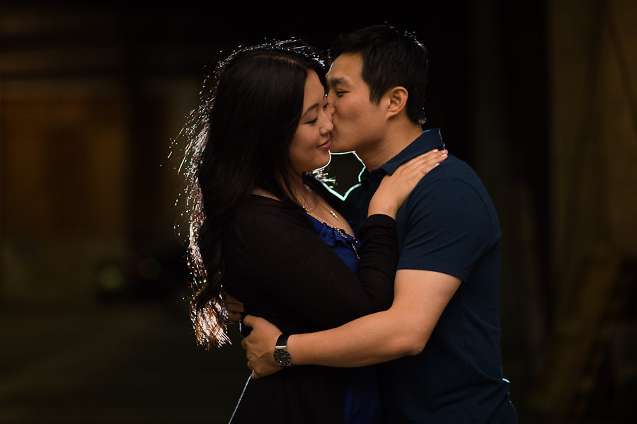 A couple embrace and share a kiss with a glint of backlight during a Pioneer Square engagement session