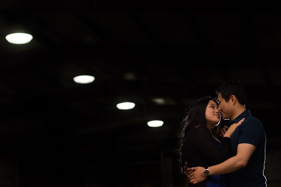 A low perspective and leading lines of ceiling lights in parking garage mixed with a hint of backlight make for an interesting image of a couple embracing during their Pioneer Square engagement session