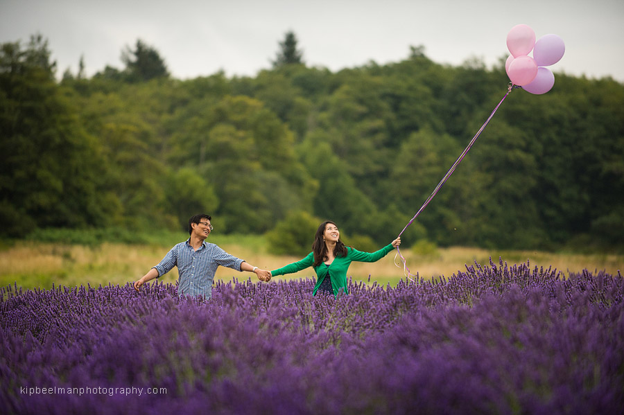 A couple with pink balloons frolicking playfully through the lavender fields of Jardin du Soleil in Sequim, WA